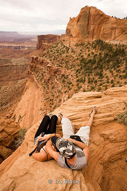 A tourist couple lying on rock at Canyonlands National Park located in southeastern Utah near the town of Moab.