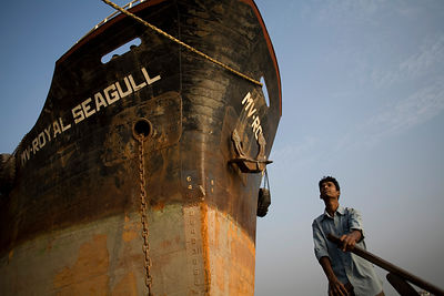 Bangladesh - Chittagong - A man pilots a boat past the hull of a large ship in the harbour