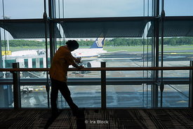 A cleaner lady wiping handrails at Changi Airport, Singapore.
