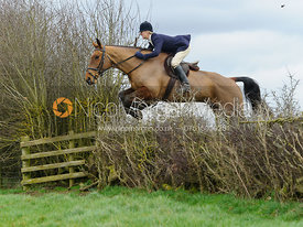 Annabel Bealby jumping a hedge above Klondike