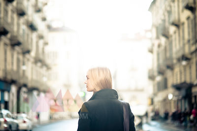 Blond woman watching something in a street