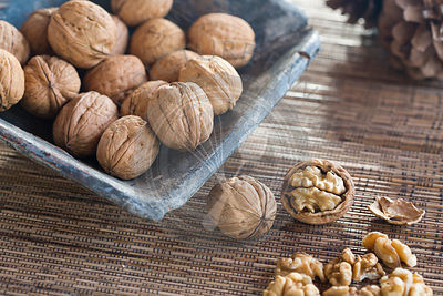 whole walnuts in a blue square ceramic dish, on woven mat, with shelled walnuts at side