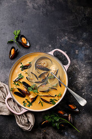 Seafood soup with shrimp and mussel in casserole on dark background copy space