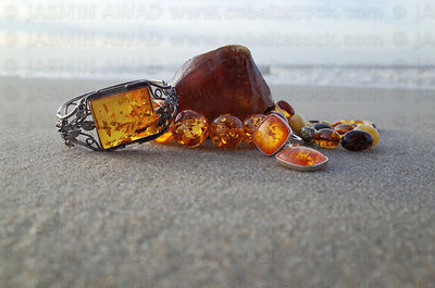 Mixed vintage jewelry with large peace of amber on the beach