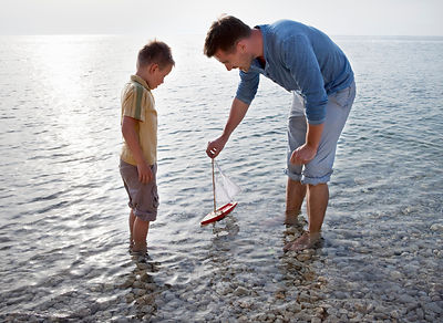 Father and son with toy boat at beach