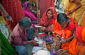 A group of women pilgrims buy cosmetics from a hawker during the Kumbh Mela, Allahabad