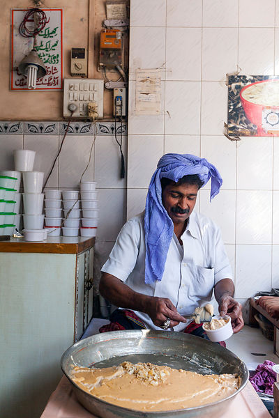 India - Delhi - Owner of the Old Kheer Shop (formerly known as 'Bade Mian') Jamal Uddin Siddique serving kheer on Lal Kuan,