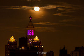 "The ""Supermoon"", the largest full moon of 2013 rises over Manhattan. The building right of center with the clock is the Con Edison Buiding, located near Gramercy Park on the east side. The pyramids of light are part of Zeckendorf Towers."