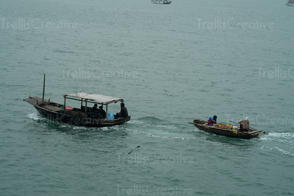 Fruit Vendor's boat and tourboat in Halong Bay, Vietnam