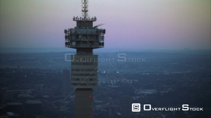 Aerial of the Hillbrow Tower moving further away to reveal Johannesburg Central Business District at sunset/sunrise. Johannesburg Gauteng South Africa