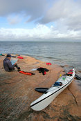 A kayaker reads a map on shore