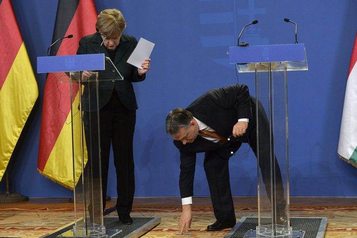 epa04600929 Hungarian Prime Minister Viktor Orban (R) picks up a pen accidential dropped by German Chancellor Angela Merkel during their joint news conference in the Parliament building in Budapest, Hungary, 02 Februrary 2015. Angela Merkel is staying in Hungary on a one-day official visit. EPA/TIBOR ILLYES HUNGARY OUT