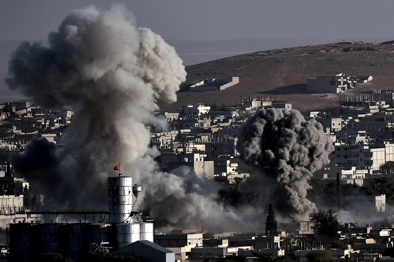 TOPSHOTS Smoke rises after strikes from the US-led coalition in the Syrian town of Ain al-Arab, known as Kobane by the Kurds, in the southeastern village of Mursitpinar, Sanliurfa province, on October 10, 2014. Coalition aircraft on Friday afternoon carried out two fresh air strikes on Islamic State (IS) jihadists in the Syrian border town of Kobane, an AFP correspondent reported. AFP PHOTO / ARIS MESSINIS