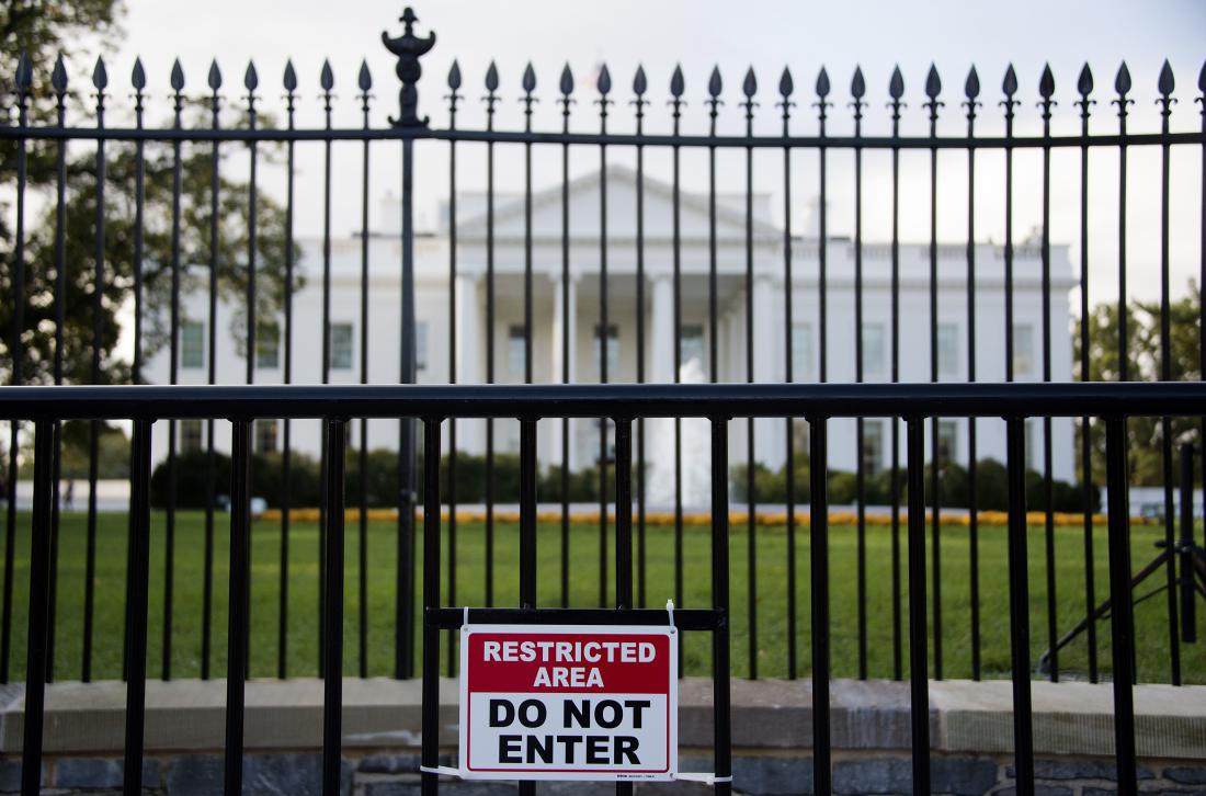 """A sign warning of a restricted area is posted on the temporary barricade in front of the fence line to the White House in Washington, DC, October 23, 2014. A suspect who climbed over the White House fence on October 22 was nabbed by Secret Service agents and dogs, a spokesman for the elite agency said. """"At approximately 7:16 pm (1116 GMT), an individual climbed the north fence line of the White House,"""" the spokesman said. """"The individual was immediately taken into custody on the north lawn of the White House by Secret Service Uniformed Division K-9 teams and Uniformed Division Officers."""" The fence climber was identified as 23-year-old Dominic Adesanya from Marlyand, near the US capital, the spokesman said. AFP PHOTO/JIM WATSON (Photo credit should read JIM WATSON/AFP/Getty Images)"""
