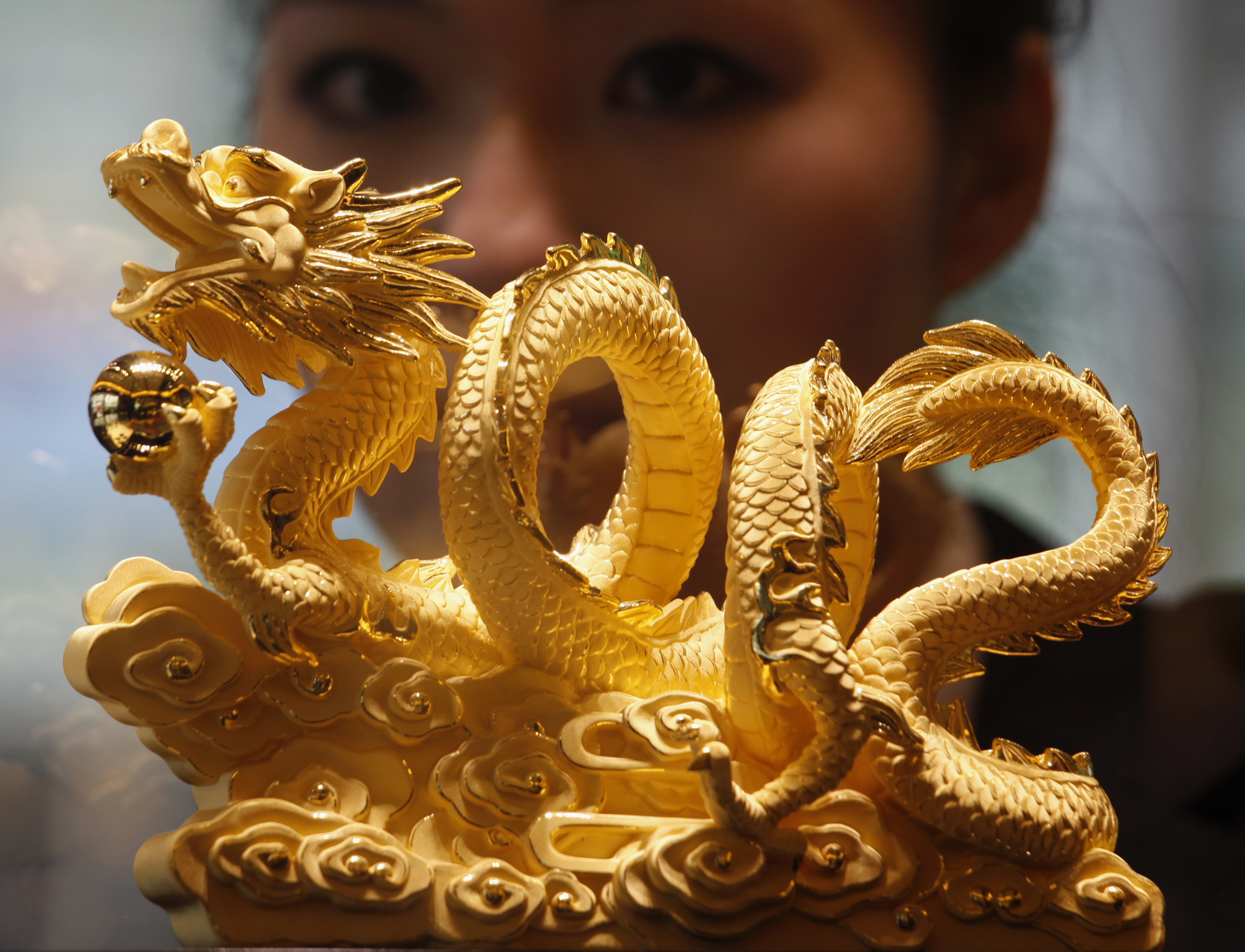 "A sales representative poses behind a nine-tael 24K gold in the shape of a dragon forming the numerals ""2012"", symbolizing the upcoming Year of the Dragon, at a Chow Tai Fook Jewellery store in Hong Kong December 6, 2011. Chow Tai Fook Jewellery, braving volatile markets with a listing in which it hopes to raise up to HK$22 billion ($2.8 billion), expects strong consumer demand in China, Hong Kong and Macau to drive sales over the next 10 years, its chairman said. REUTERS/Bobby Yip (CHINA - Tags: BUSINESS COMMODITIES SOCIETY WEALTH) - RTR2UWBQ"