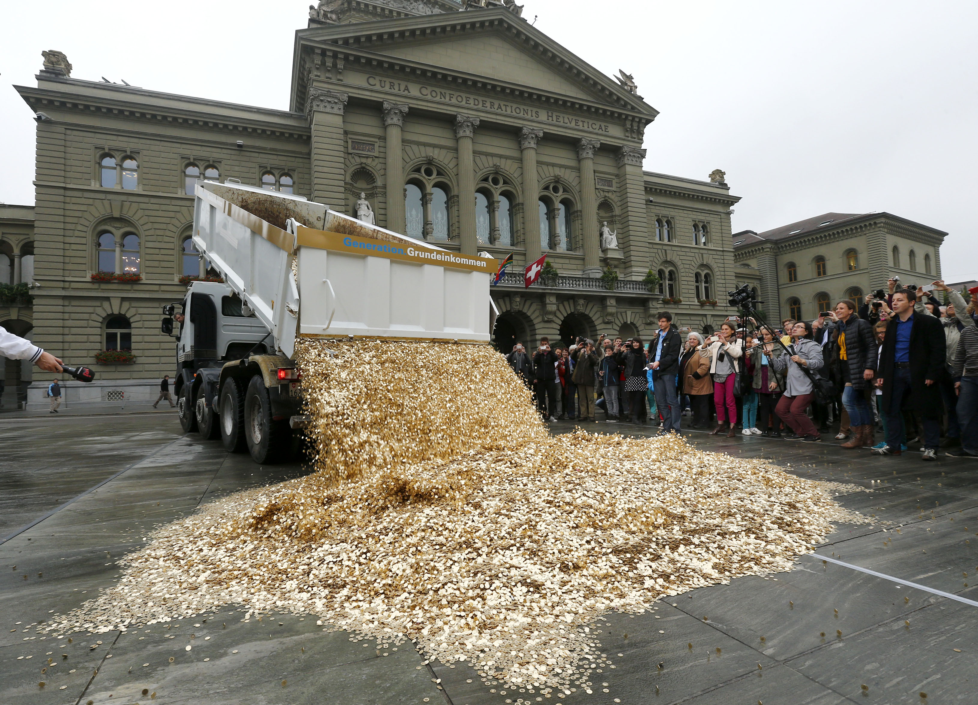 """A truck dumps five cent coins in the centre of the Federal Square during a an event organised by the Committee for the initiative """"CHF 2,500 monthly for everyone"""" (Grundeinkommen) in Bern October 4, 2013. The Committee delivered 126,000 signatures to the Chancellery on Friday to propose a change in the constitution to implement their initiative. The initiative aims to have a minimum monthly disposal household income of CHF 2,500 (US$ 2,700) given by the government to every citizen living in Switzerland. REUTERS/Denis Balibouse (SWITZERLAND - Tags: POLITICS CIVIL UNREST) - RTR3FL4O"""