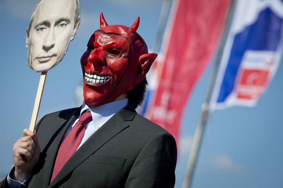 An activist wore a devil's mask which he covered with a picture of Vladimir Putin as part of a protest against the Russian President outside the congress center of the Hanover trade fair on Sunday in Hanover, western Germany.