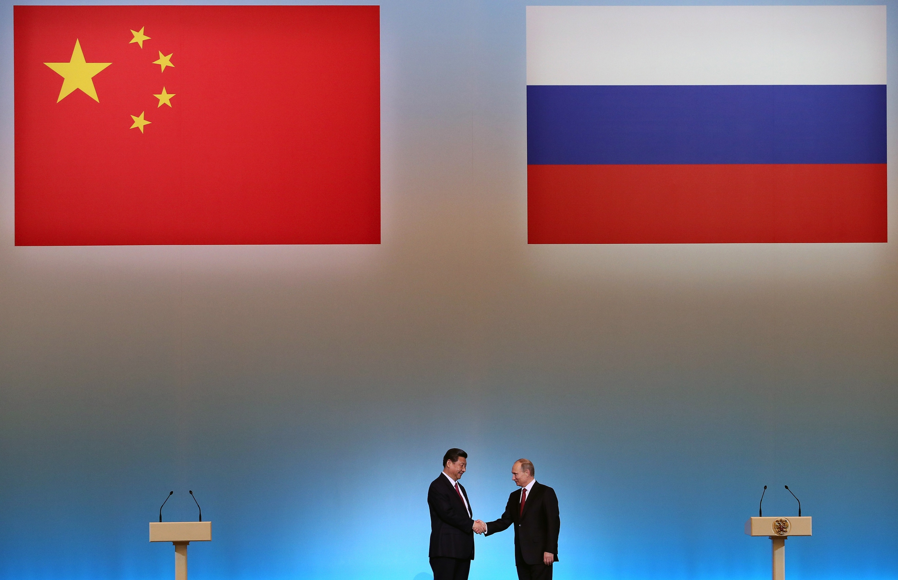 "China's President Xi Jinping (L) is welcomed by his Russian counterpart Vladimir Putin (R) during the opening ceremony of ""The Year of Chinese Tourism in Russia"" in Moscow, on March 22, 2013. China's new president Xi Jinping arrived today in Moscow on his first foreign visit since assuming the presidency earlier this month. Xi Jinping and his counterpart Vladimir Putin are set to oversee the signing of a number of energy and investment agreements including a deal that will see Russia ramp up oil supplies to China. AFP PHOTO / POOL / SERGEI ILNITSKY (Photo credit should read SERGEI ILNITSKY/AFP/Getty Images)"