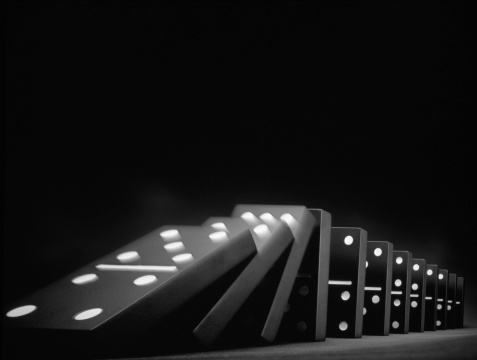 Row of dominoes falling down (B&W, long exposure)