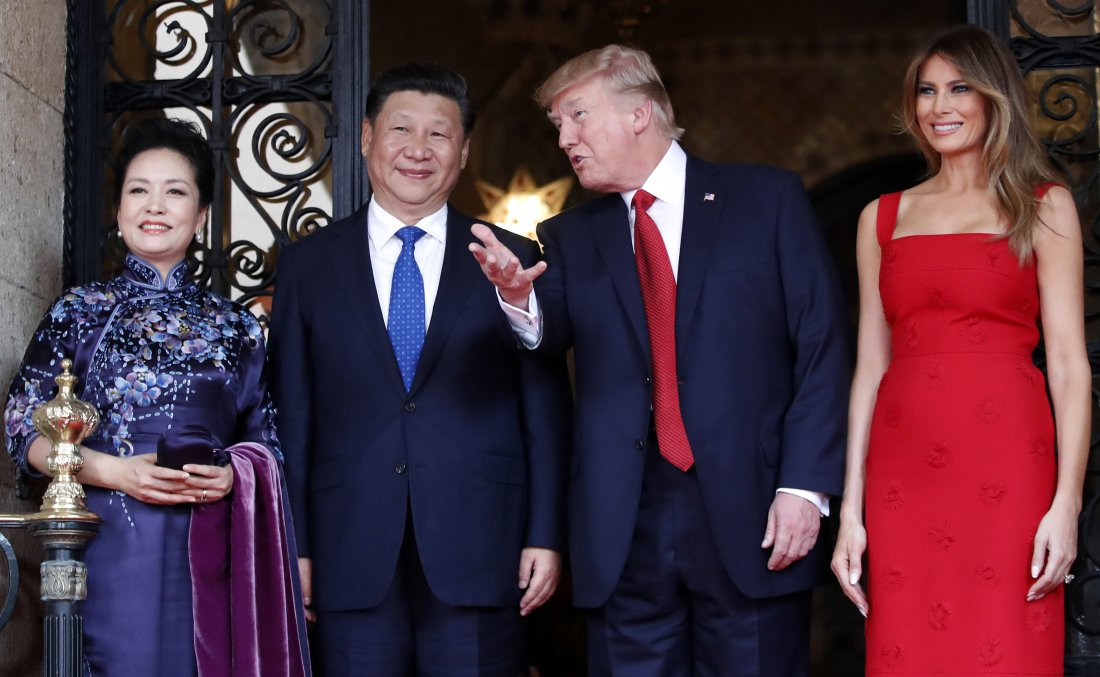 President Donald Trump talks with Chinese President Xi Jinping, with their wives, first lady Melania Trump and Chinese first lady Peng Liyuan as they pose for photographers before dinner at Mar-a-Lago, Thursday, April 6, 2017, in Palm Beach, Fla. (AP Photo/Alex Brandon)