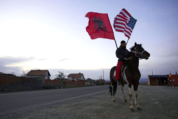 PRISTINA, SERBIA - FEBRUARY 16: Kosovo-Albanian waves an Albanian and a American flag when he ride a horse during the celebration of Kosovo's expected declaration of independence on February 16, 2008 in Pristina, Kosov. Prime Minister Hashim Thaci is expected to declare independence from Serbia on Sunday, a move supported by the major EU nations and the United States which will be categorically rejected by Serbia and Russia. (Photo by Carsten Koall/Getty Images) independence Kosovo