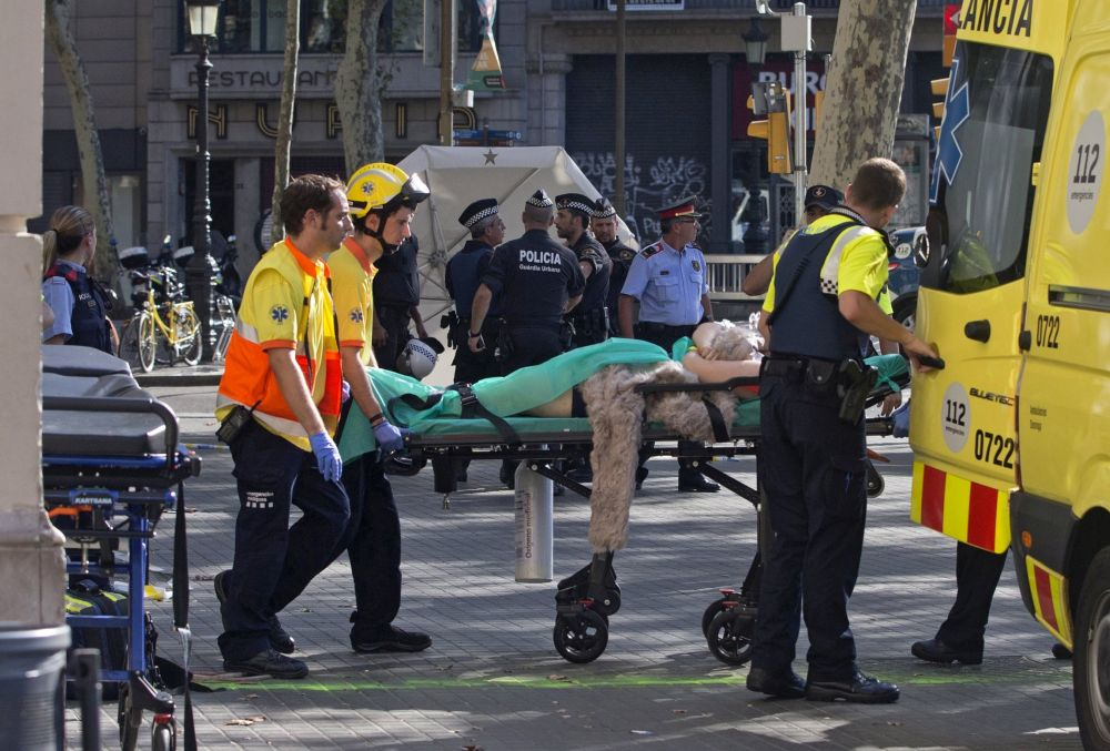 epa06148678 Mossos d'Esquadra Police officers and emergency service workers move an injured after a van crashes into pedestrians in Las Ramblas, downtown Barcelona, Spain, 17 August 2017. According to initial reports a van crashed into a crowd in Barcelona's famous Placa Catalunya square at Las Ramblas area injuring several. Local media report the van driver ran away, metro and train stations were closed. The number of people injured and the reasons behind the incident are not yet known. Official sources have not confirmed that the incident is a terrorist attack. EPA/Quique Garcia FACES PIXELATED BY SOURCE DUE TO LOCAL LAW