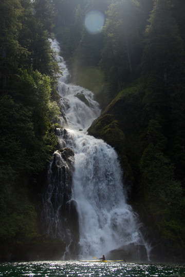 Kayaker under waterfall in the Tongass National Forest. Photo courtesy of the Sitka Conservation Society.