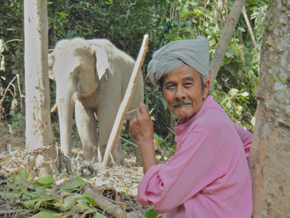 Malaysian villager with elephant behind him. Photo courtesy of Ahimsa Campos-Arceiz.