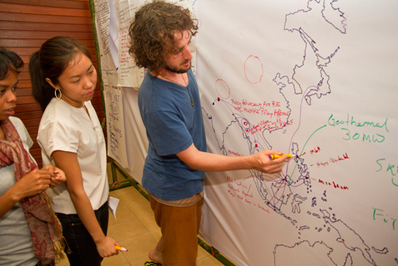 Participants from diverse backgrounds and groups marking on a map the creation of partnerships through identified projects at the end of the Southeast Asia Renewable Energy People's Assembly (SEAREPA) at the Rainforest Discovery Centre in Sandakan, Sabah. Photo by: Suzanne Chong/LEAP.