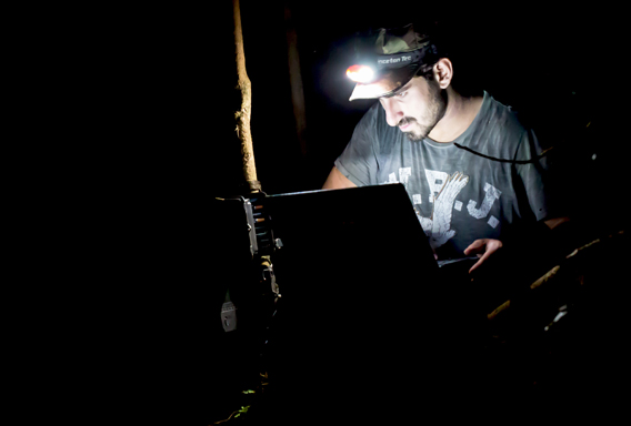 Paul Rosolie checking the camera trap videos on a laptop in the Amazon. Photo by: Mohsin Kazmi