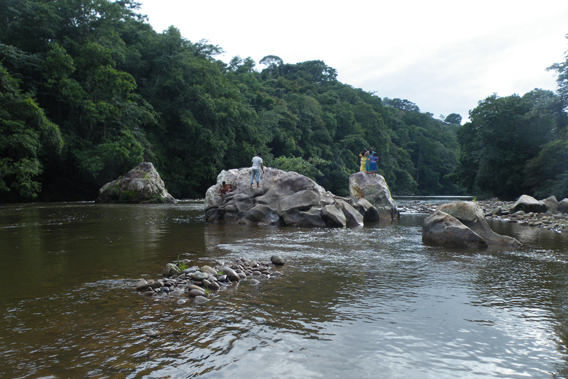 Ngabe on boulders containing petroglyphs, in the Tabasara River. The boulders will be drowned by the dam. Photo courtesy of Robin Oisín Llewellyn.