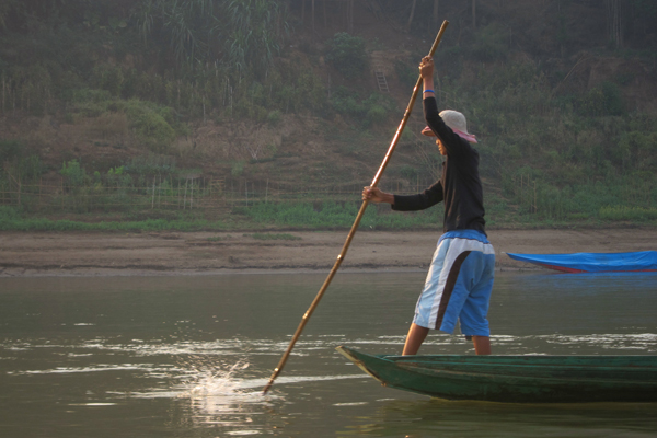 Fisherman navigating the river in Lao PDR. Photo courtesy of FISHBIO.