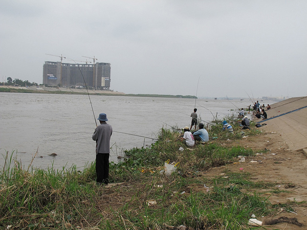 Fishing along the increasingly urbanized Mekong. Photo courtesy of FISHBIO.