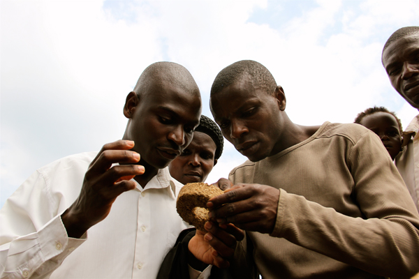 Locals investigating a  biomass briquette. Photo courtesy of New Nature Foundation.