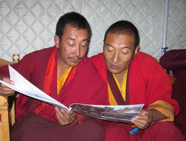 Monks reading snow leopard field guide. Photo by: Panthera (T. McCarthy).