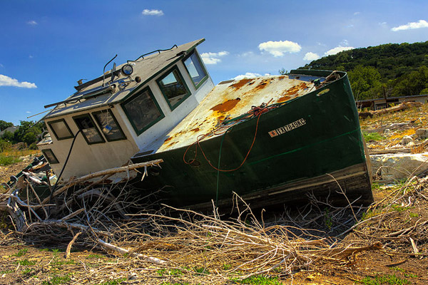 Texas has been hit hard by drought since 2010. Here, a boat languishes in Lake Travis, part of the Colorado River. Photo by: Erik A. Ellison.