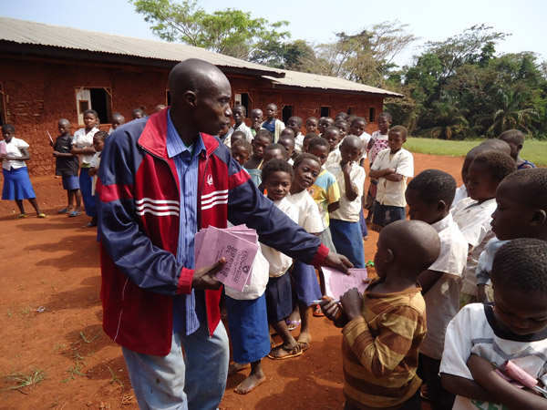 Distributing school supplies. Photo courtesy of the Okapi Conservation Project.