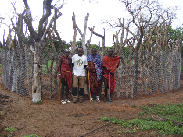 RCP Senior Researcher Monty Kalyahe stands in front of a boma (livestock enclosure) reinforced by RCP staff for a Maasai family. RCP's reinforced bomas thus far have been 100% effective at protecting livestock from depredation. Photo by: Jon Erickson.