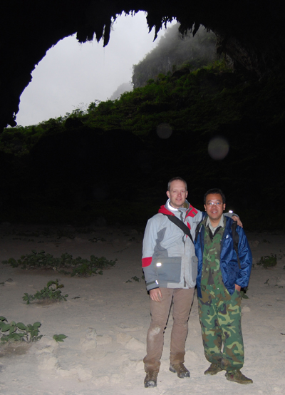 Botanists Wei Yi-Gang, Guangxi Institute of Botany, and Alex Monro, Royal Botanic Gardens Kew, standing within Yangzi cave with clumps of plants from the nettle family nearby. Photo by: Alex Monro.