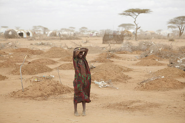 A girl stands in front of freshly dug graves in Dadaab, Kenya. The town was one of the places Somali refuges fled to during the 2011 famine, but many didn't make it. Most of the dead were children. Photo by: Andy Hall/Oxfam East Africa.