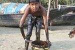 Children 'clean' oil spill with kitchen utensils in the Sundarbans