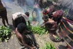 Tribal Dani wanita memasak ubi jalar