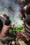 Dani women cooking sweet potato