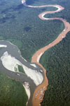 Mine waste-laden stream flowing into a rainforest river in Peru