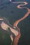 Aerial view of a muddy, mine waste-laden stream flowing into a rainforest river