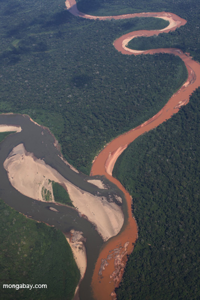 Aerial view of a muddy, mine waste-laden stream flowing into a rainforest river. Photo by: Rhett A. Butler.