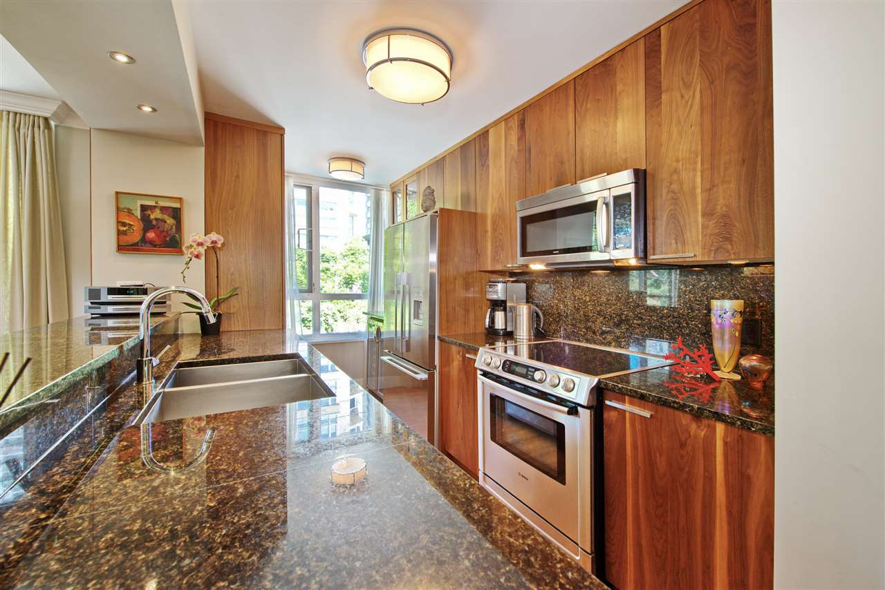 Custom walnut cabinetry runs up to ceiling and provides extensive storage, pantry, recycling drawer enhanced by rich toned high quality granite