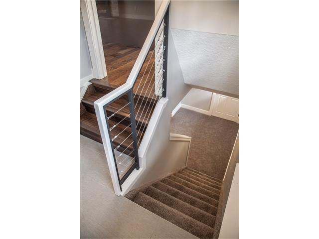 Stairs leading to basement with unique style railing