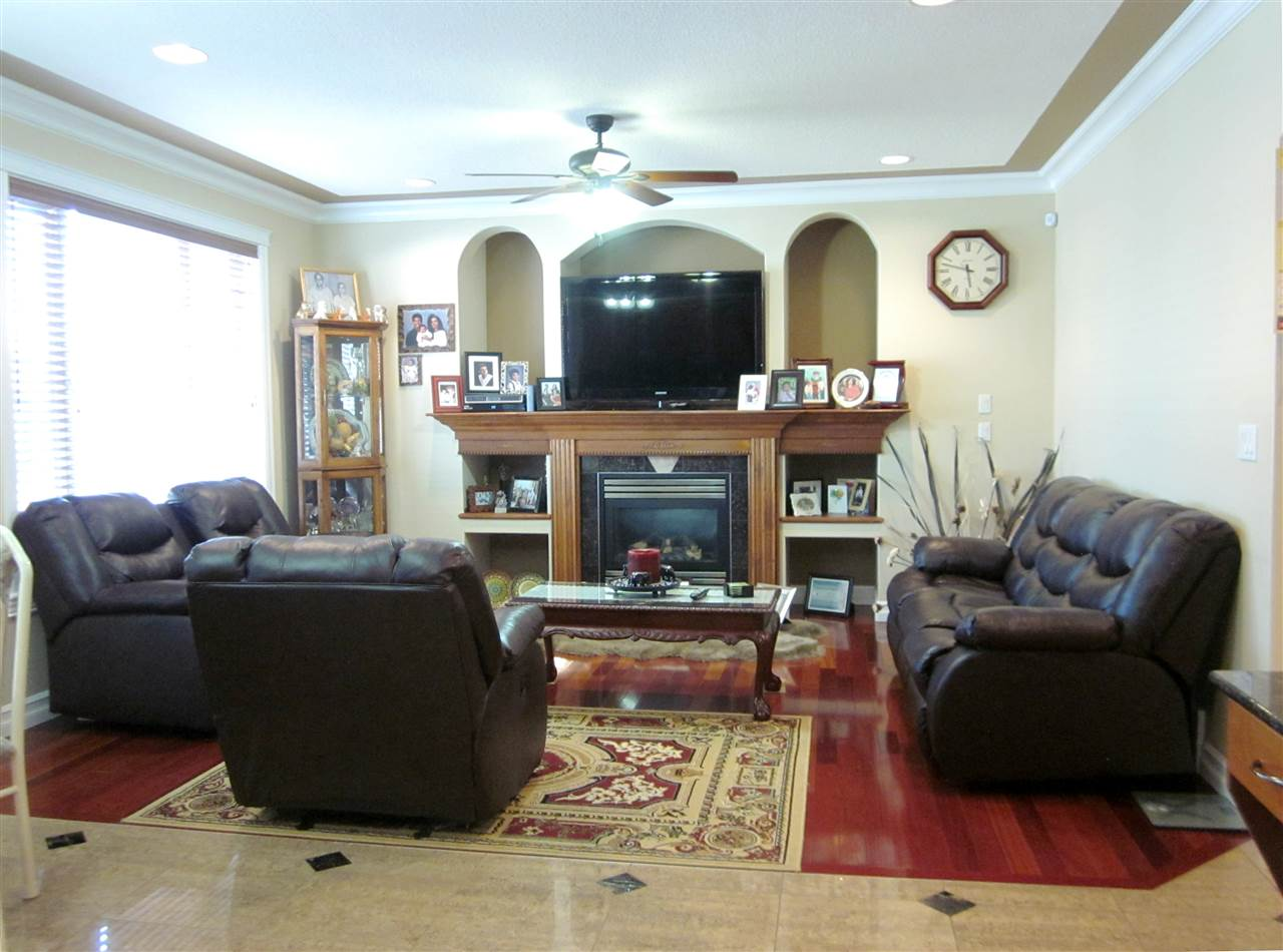 Large and bright family room with gas fireplace and hardwood flooring.