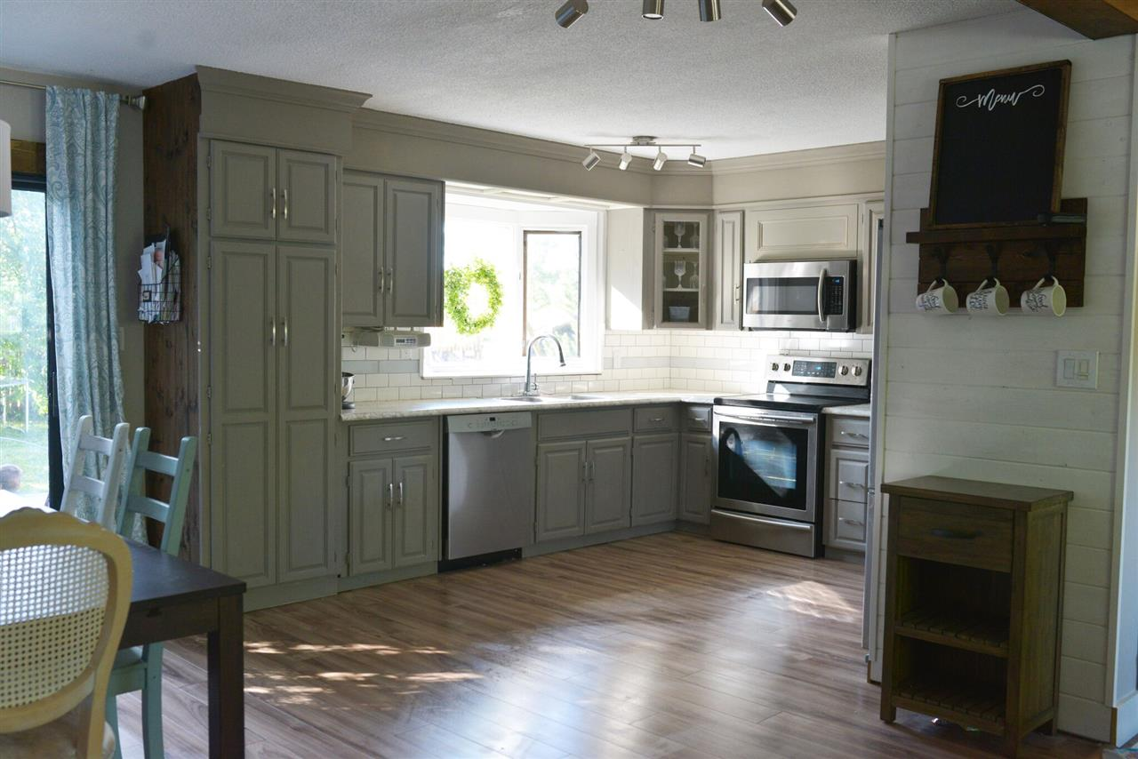 The huge kitchen has plenty of prep and storage space. It has been given a refresh with gray painted cabinets, new counters, appliances, hardware and back-splash!